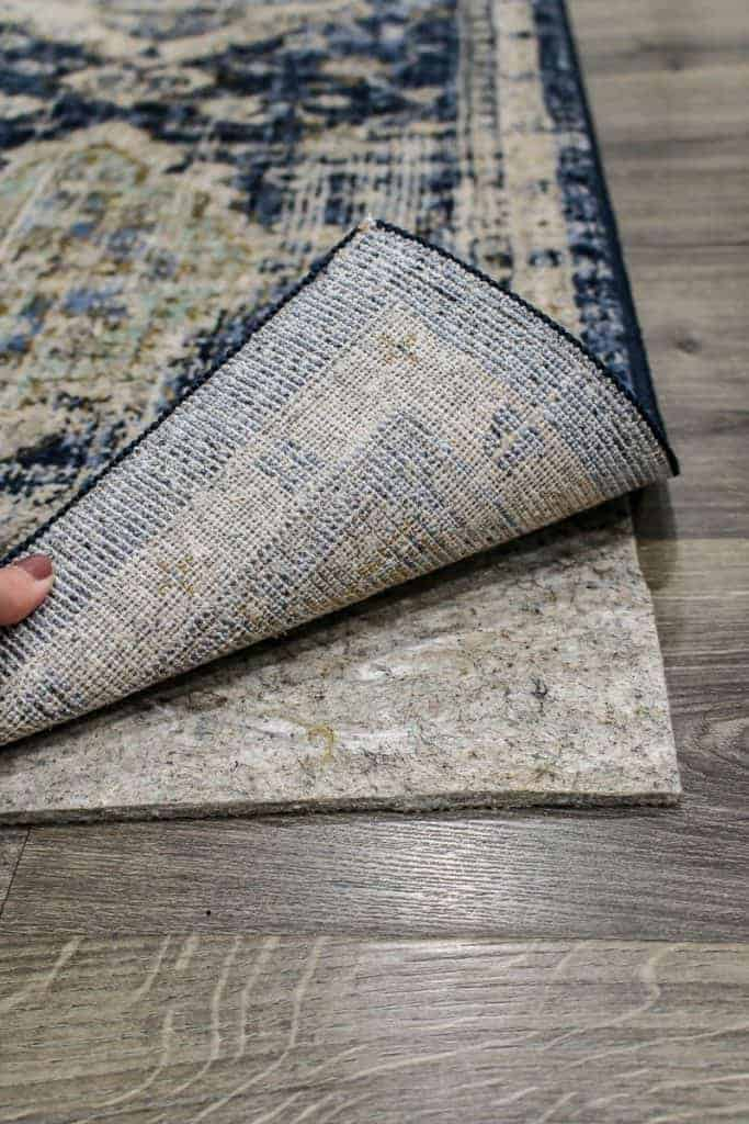 shows the Pantaleone Indigo Runner Area Rug being lifted up to shows a rug pad on gray wood floors