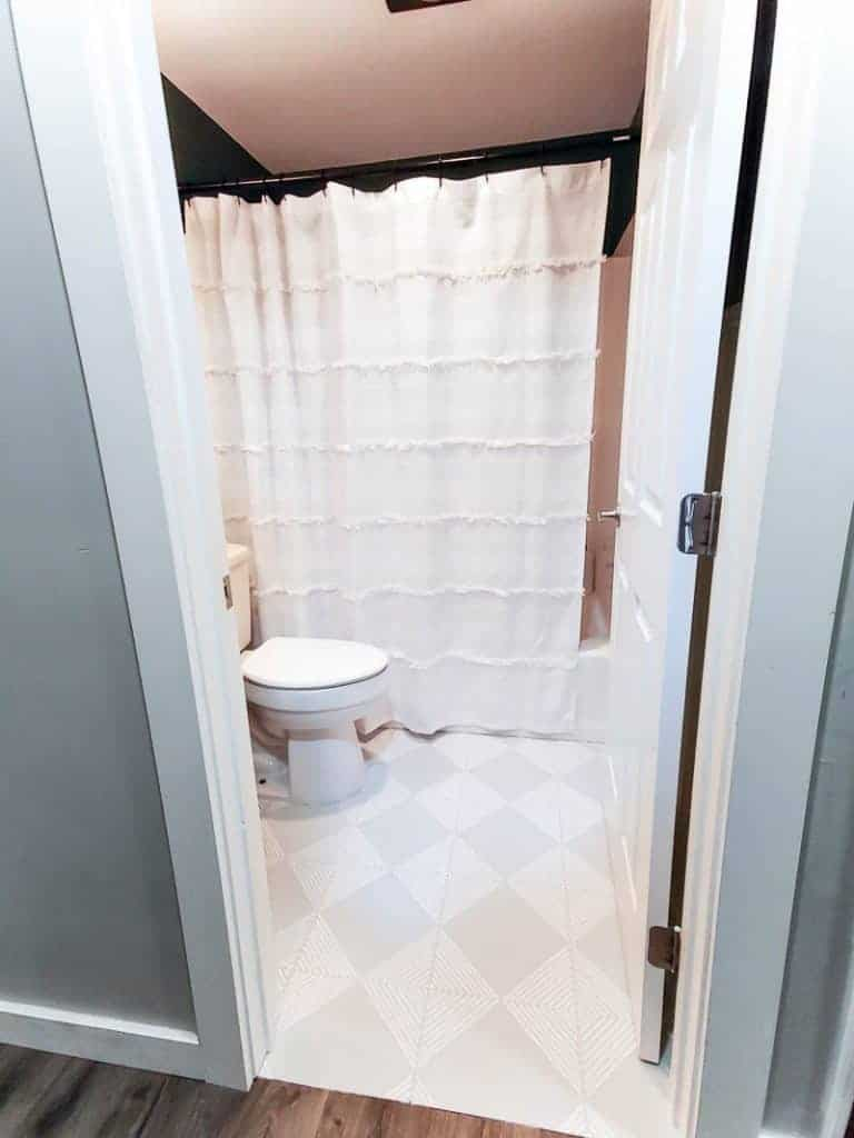 shows the bathroom with gray and white striped floors and white shower curtain and teal walls from the outside