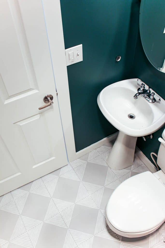 shows a teal walled bathroom with gray floors with white stripes from a downward angle