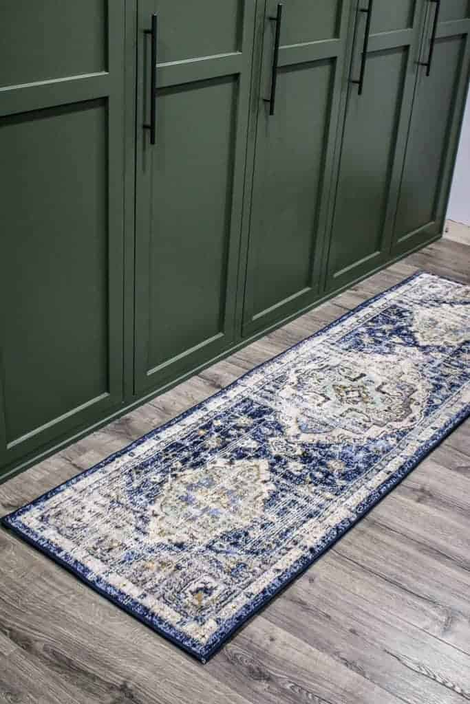 shows green mudroom lockers with a Mohawk Home Pantaleone Indigo Runner Area Rug on gray wood floors
