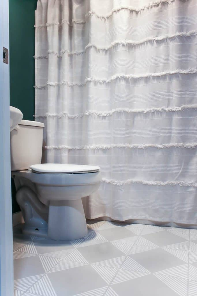 shows a teal walled bathroom with a white toilet and shower curtain with gray floors with white stripes