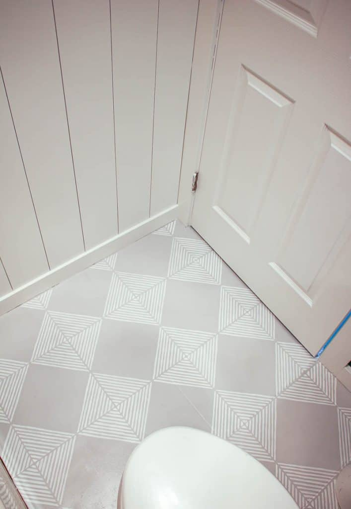 shows gray tile floors with white stripes and a white wood wall and white door