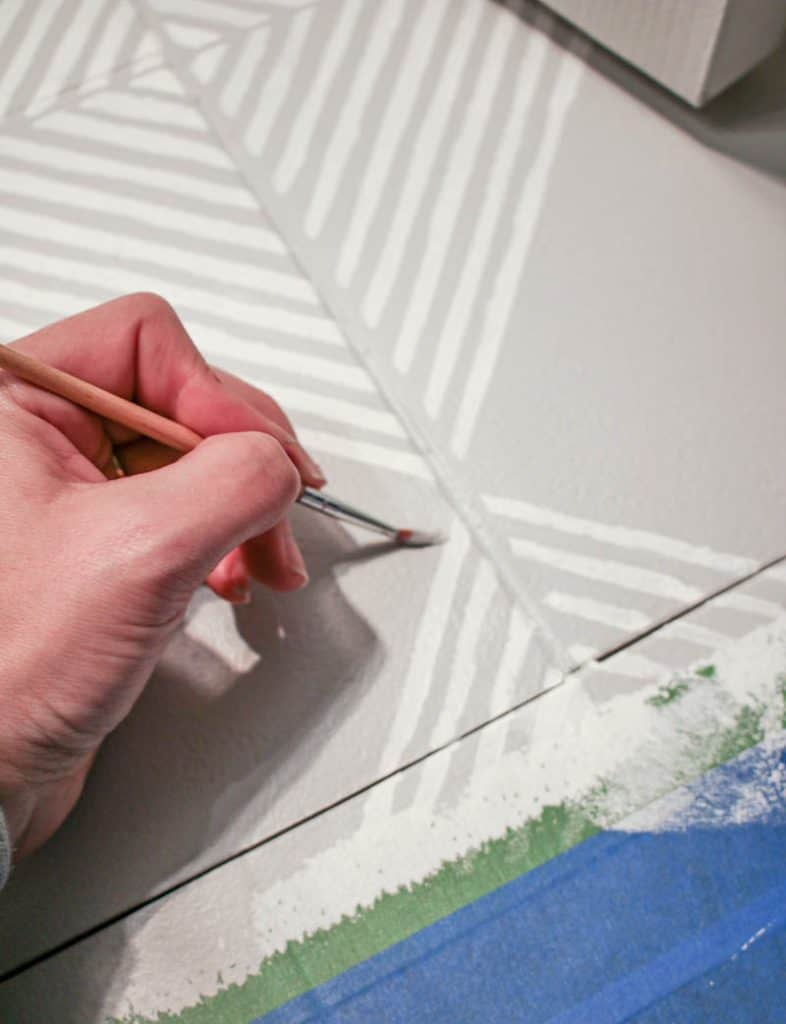 shows a hand touching up stencil by painting white stripes on a gray tile floor