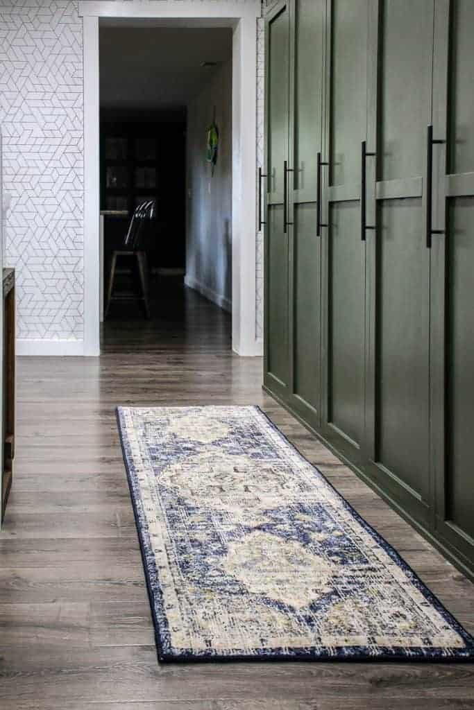 shows a green farmhouse mudroom with gray floors and white walls with a blue/tan vintage inspired boho runner rug