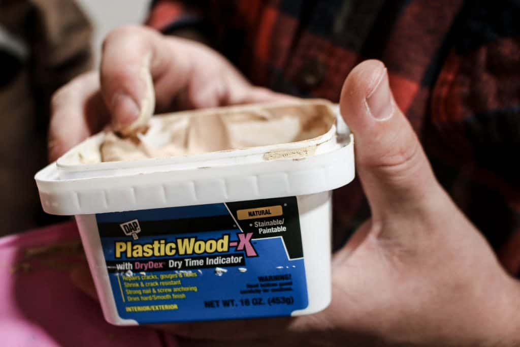 shows a finger wiping off some DAP Plastic Wood-x in the edge of the container