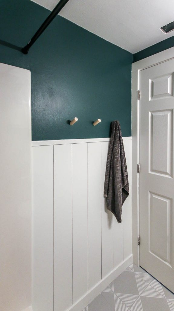shows an angled view form the tub of the white vertical shiplap all with top half painted dark green and white door with gray floors with white stripes
