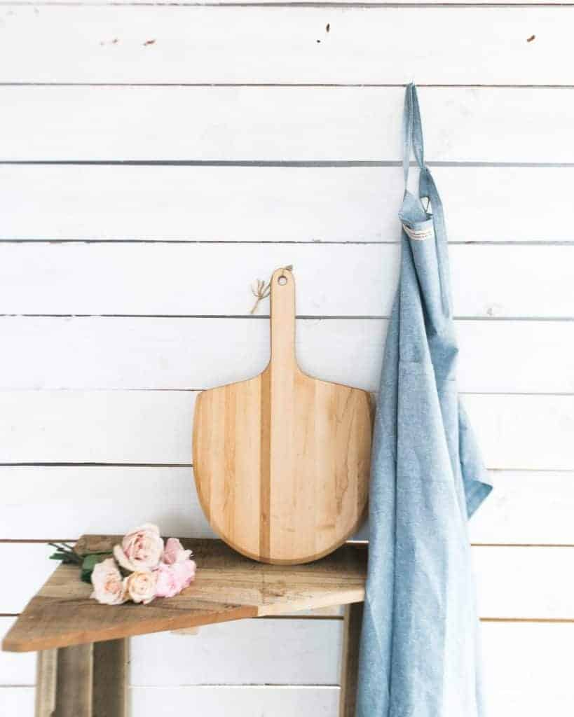 rustic shiplap wall painted white with wooden stool and wooden cutting board and roses on it with a blue apron hanging on the wall