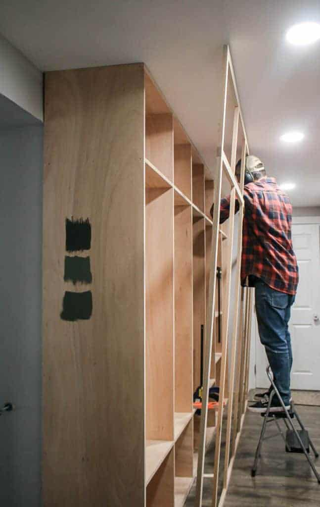 shows a man holding up a face frame while attaching to build in mudroom cabinets on a step ladder in a hallway with gray wood floors