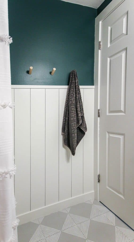 shows an angled view of white vertical shiplap wall in a small bathroom with top half being dark teal with a white door and shower curtain, wood towel hooks and gray floors with white stripes