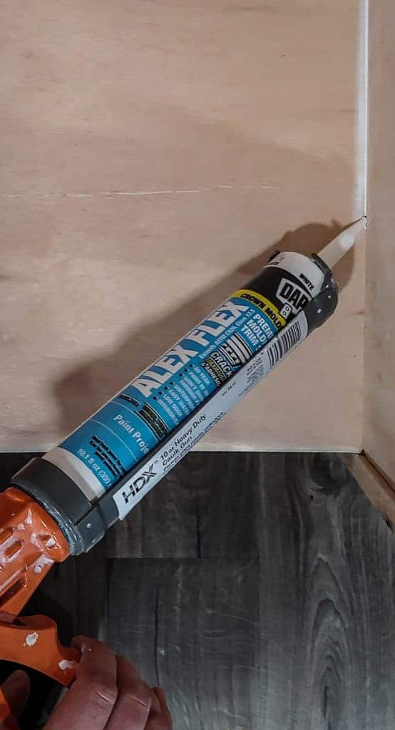 shows the brand DAP Alex Flex caulk being squeezed in between to panels of plywood