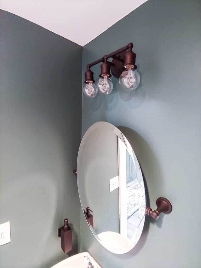 shows a side angled view a dark teal bathroom with an oval mirror and farmhouse styled vanity lights