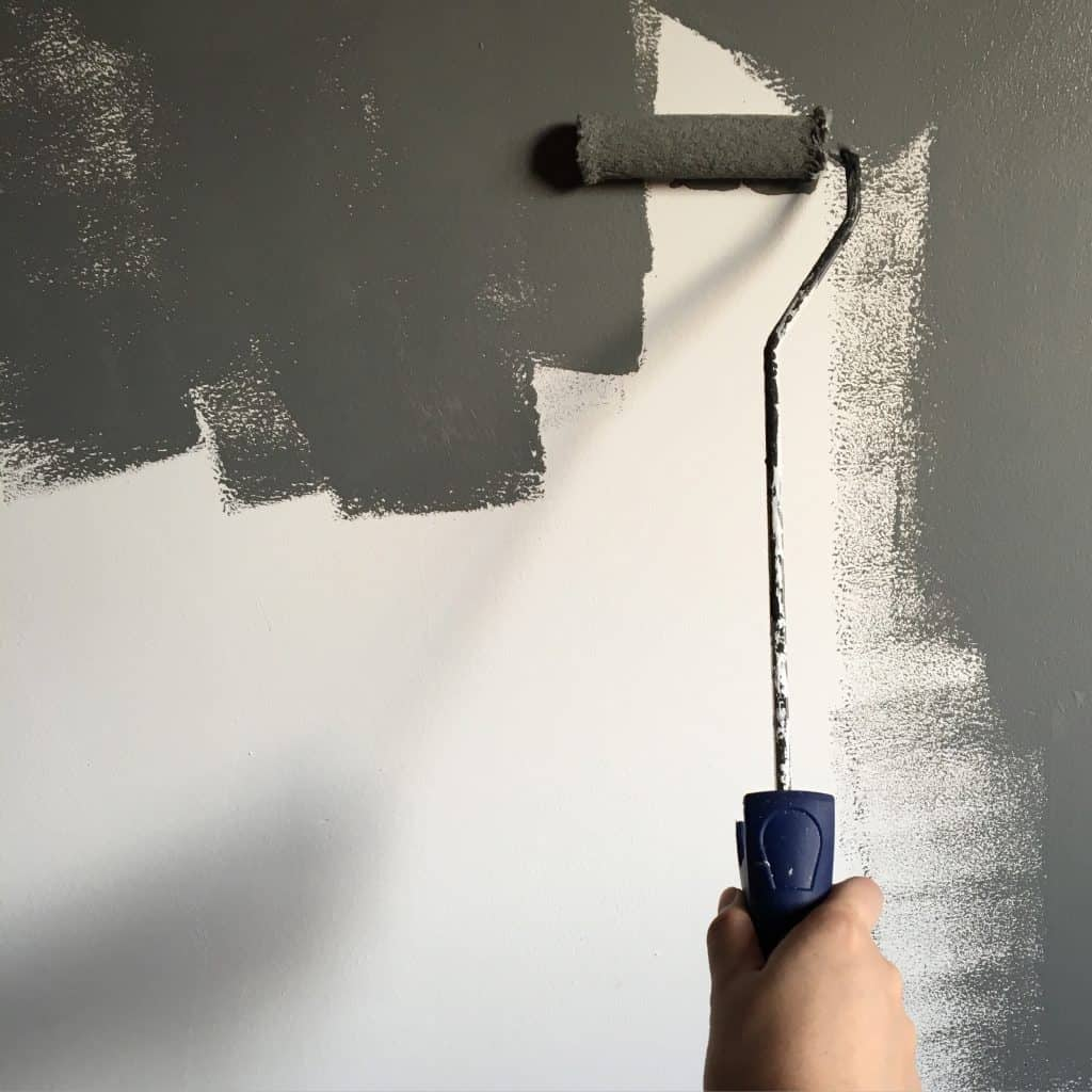 shows a paint roller painting a white wall with dark gray