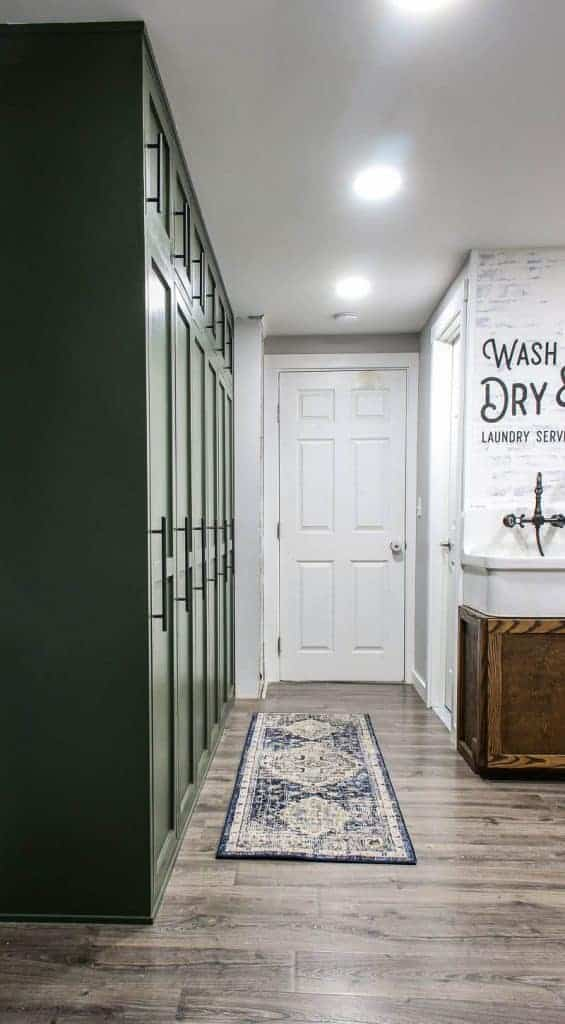 shows a farmhouse green mudroom lockers with blue and white boho runner rug on the gray wood floors in a white hallway and door with wash and dry laundry service stenciled on the wall