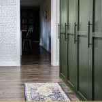 Olive green mudroom lockers with shaker style doors and modern famrhouse hardware with vintage inspired runner rug and text overlay that says mudroom lockers