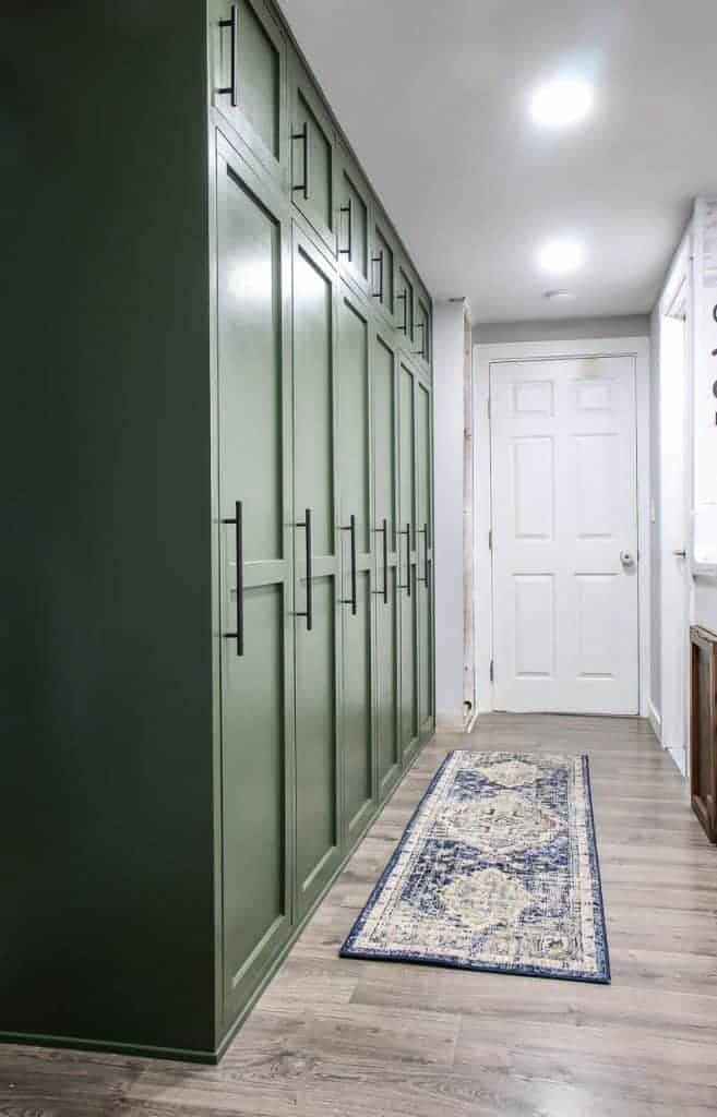shows a farmhouse green mudroom lockers with blue and white boho runner rug on the gray wood floors in a white hallway and door