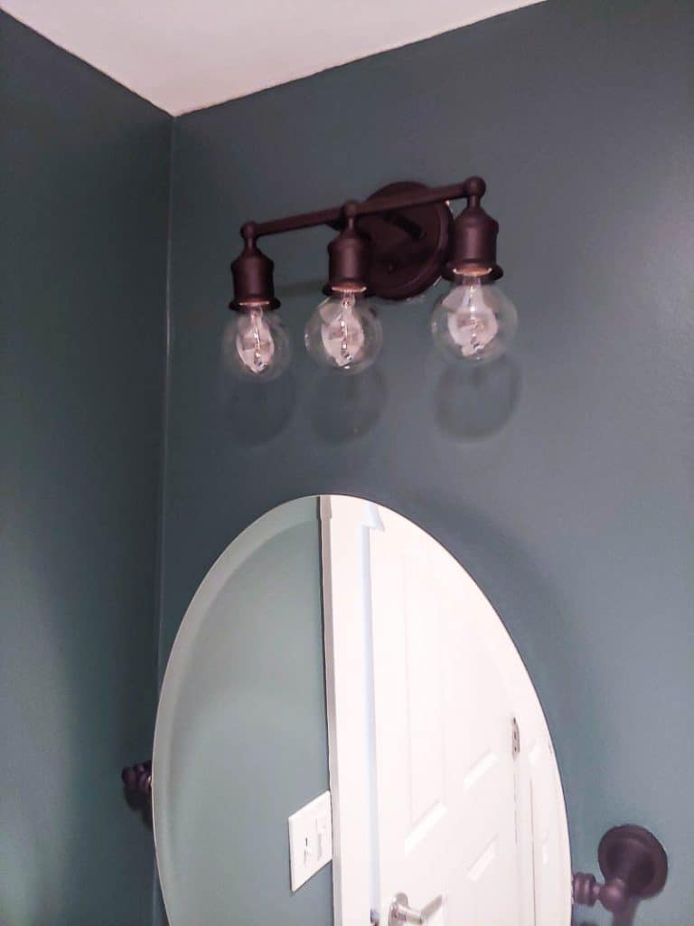 shows a dark teal bathroom with an oval mirror and farmhouse styled vanity lights