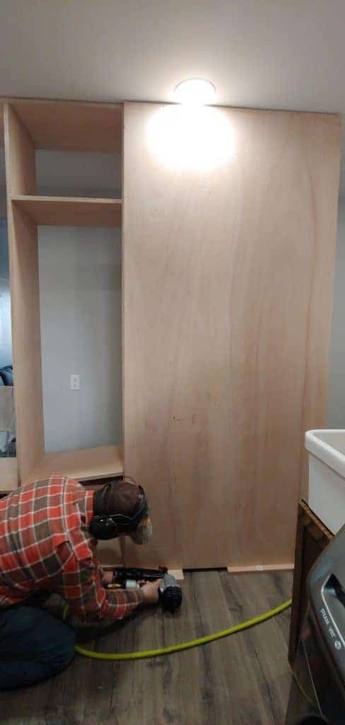 shows a man nailing the back of the mudroom lockers on