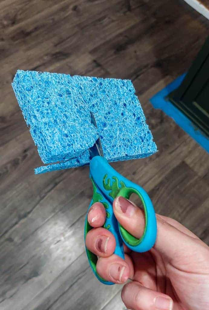 shows a pair of green and blue scissors cutting a blue sponge into a semi circle in half over wood floors