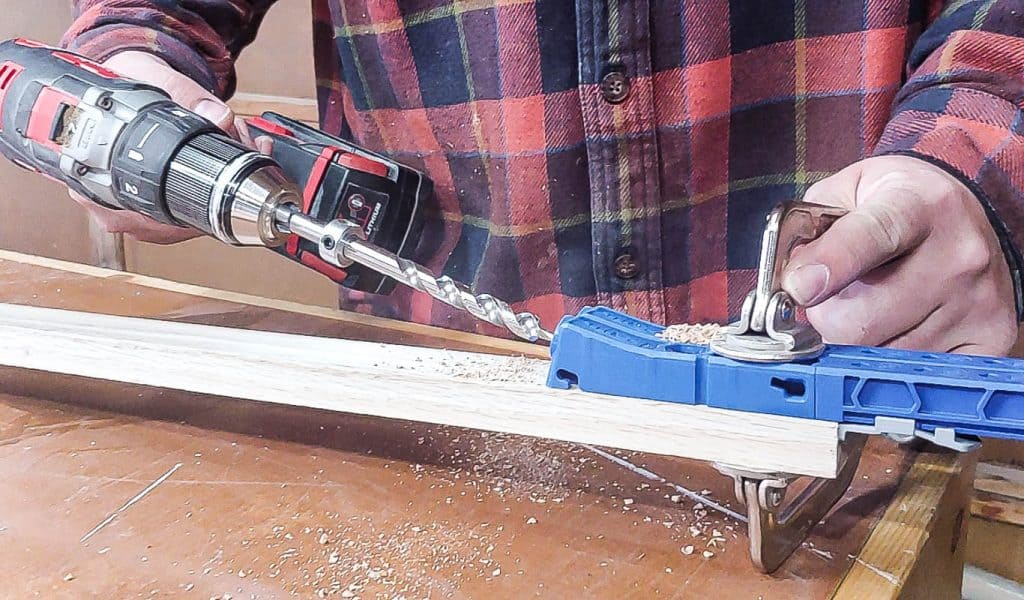 shows a person using a Kreg 320 to drill pocket holes into a piece of wood on a wood table