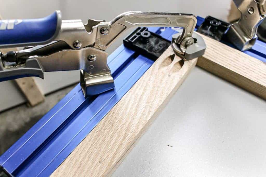 shows a piece of wood clamped down on the Kreg clamp table with two pocket holes in it