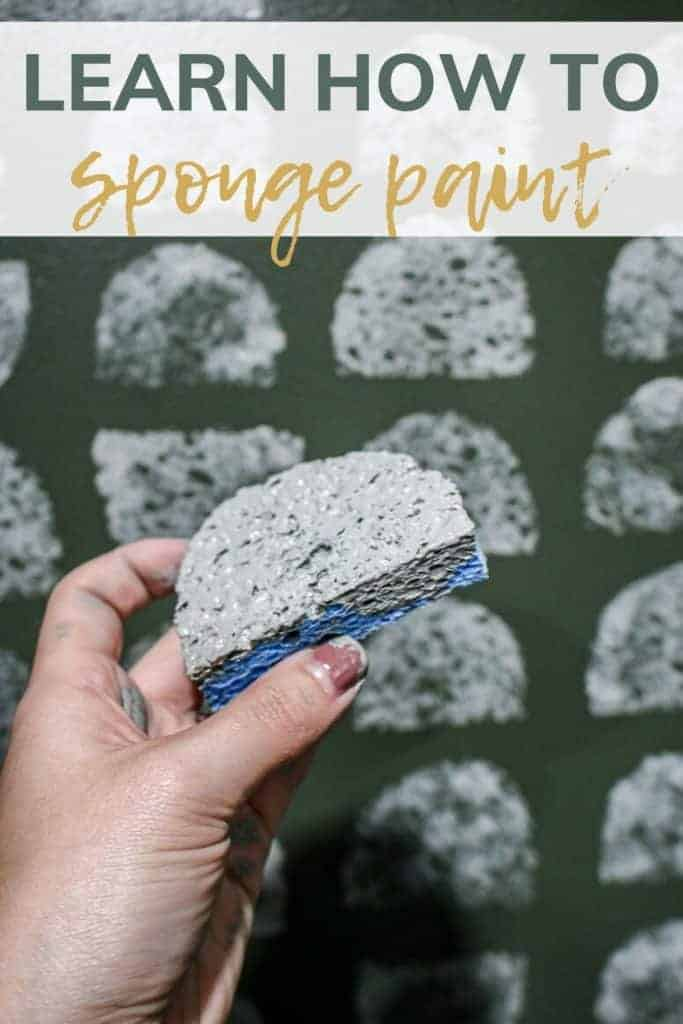 shows a hand holding a half circle sponge with gray paint on it and in the background the wall is painted green with gray half circles with overlay text that says learn how to sponge paint