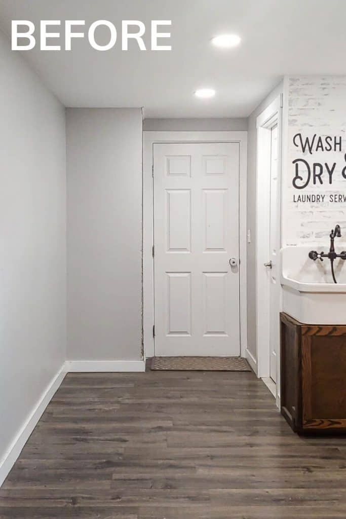 Shows the side of laundry room with white walls with Wash and Dry laundry service stencil and gray wood floors and farmhouse sink with text that says before