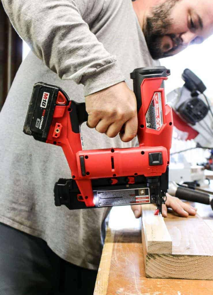 shows a man in a gray long sleeve using a cordless Milwaukee m18 nailer on a piece of wood on a table and a table saw in the background