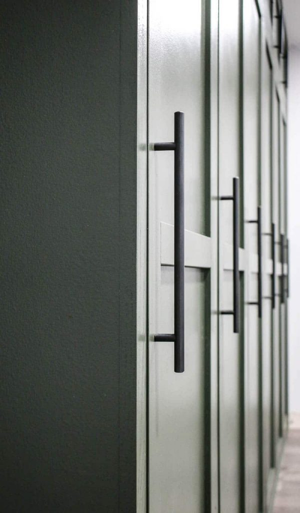 shows a closer up view of the green mudroom locker doors with oil rubbed bronze pulls