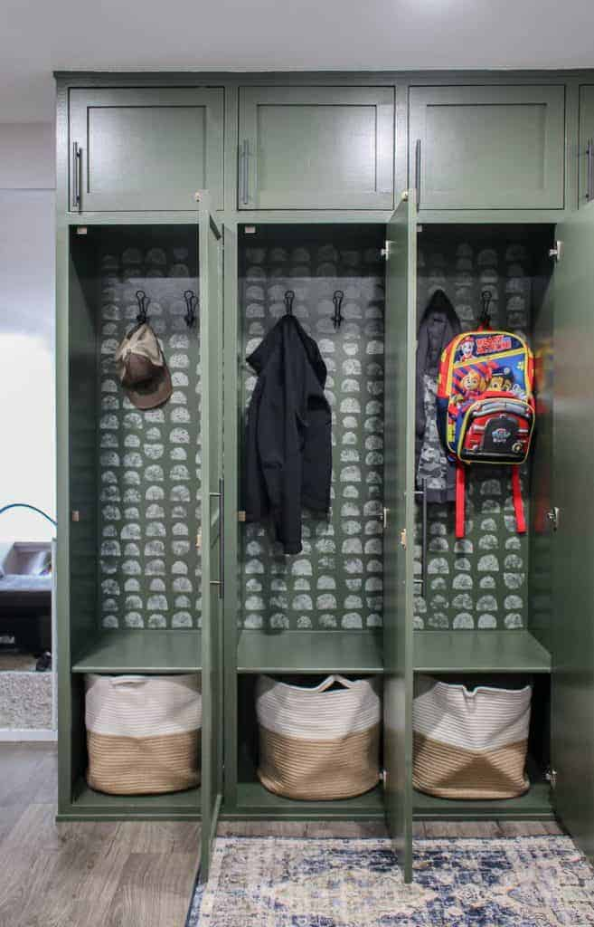 shows a picture of the mudroom lockers with the doors open that shows a hat, jackets, and a backpack hanging from the hooks and white and tan bags sitting in the bottom with gray half circle pattern painted on the back of the lockers