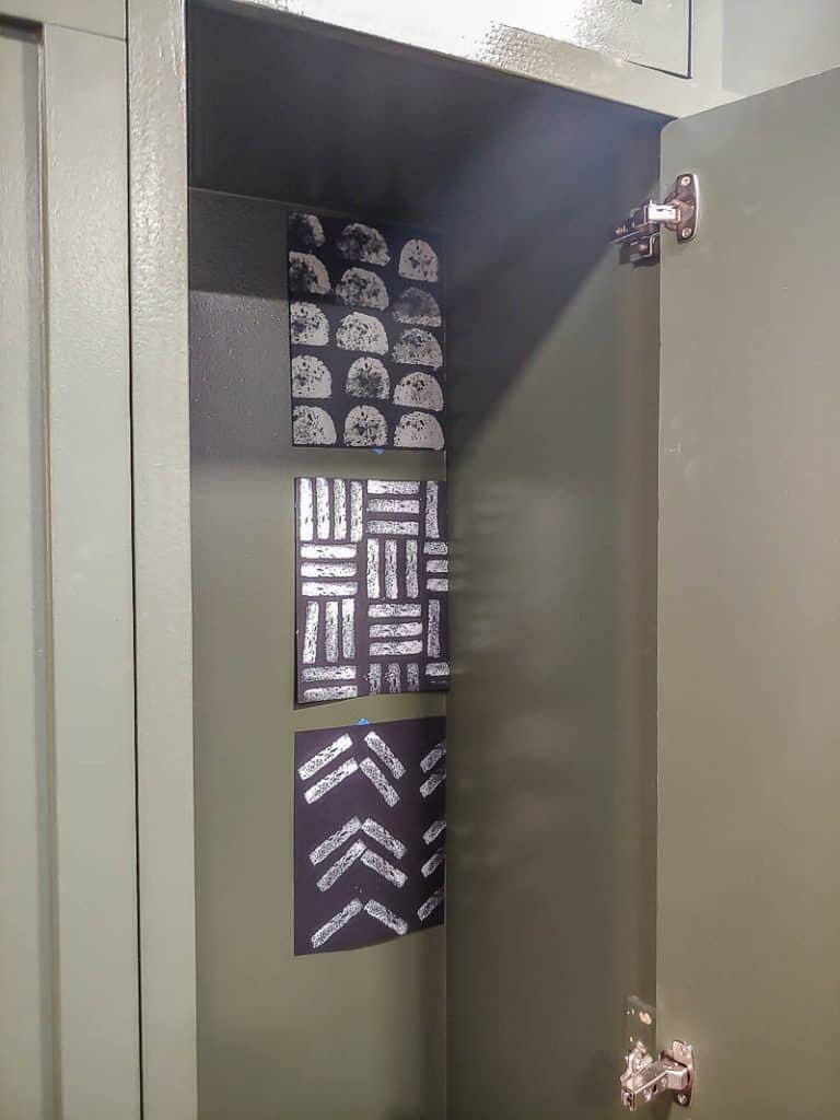 shows the inside of a green mudroom locker with different variations of sponge paint patterns to test out