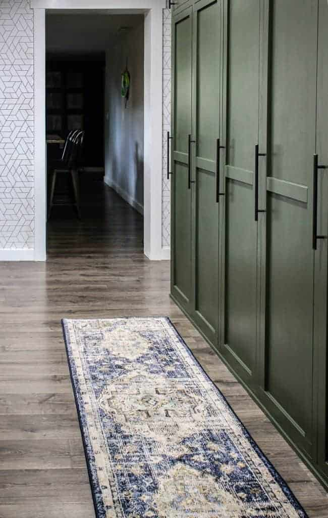 shows a farmhouse green mudroom lockers with blue and white boho runner rug on the gray wood floors in a white wallpapered wall and kitchen in background