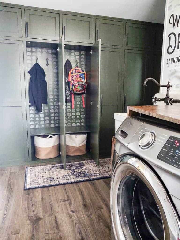 shows a farmhouse laundry room with green farmhouse mudroom lockers with some jackets and backpacks with white sponge painted spots in the back with a boho runner rug on the gray wood floors