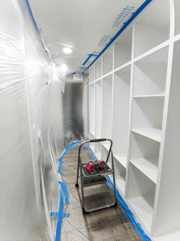 shows a hallway covered in plastic and tape with the mudroom painted white with primer and a step ladder