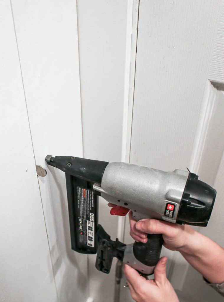 shows a nail gun pressing into a white shiplap installing on a wall vertical with a nickel used as a spacer between the planks