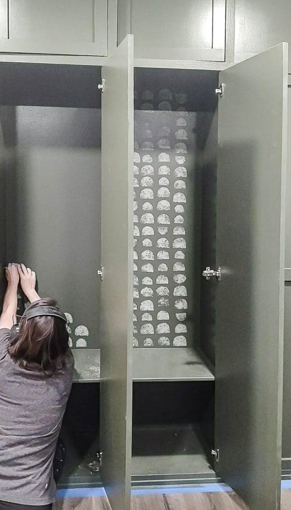 shows a woman stamping the back of the mudroom lockers with a gray painted half circle pattern with a finished locker on the other side