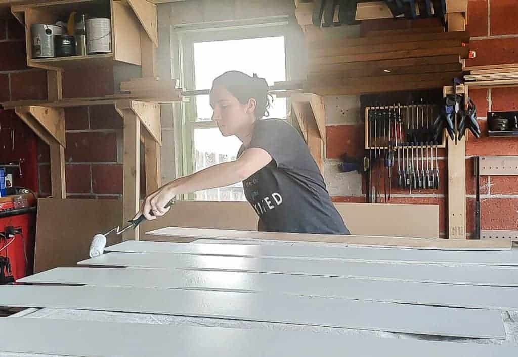 shows a woman painting the shiplap planks white in a garage