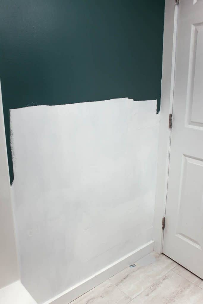 shows a teal wall painted white with primer about halfway up with a white door before shiplap is installed