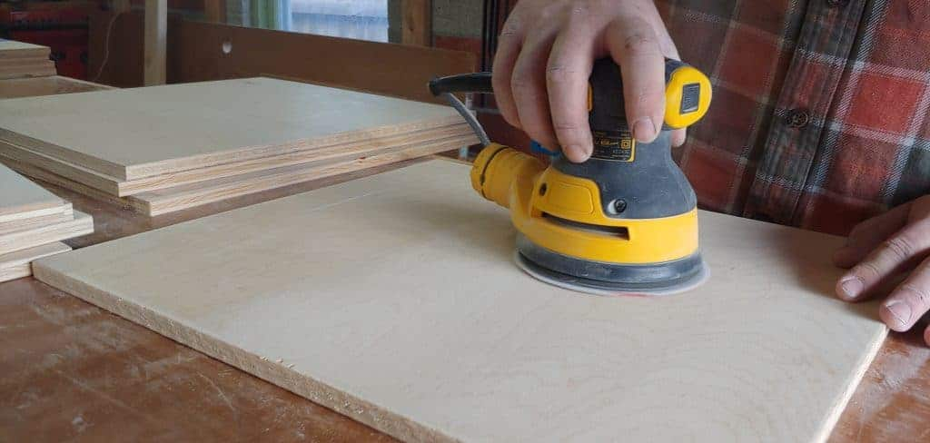shows a hand using a sander to smooth out the square piece of plywood