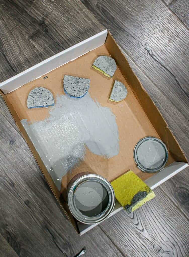 shows a cardboard box lid with gray paint and sponges cut in half circles on gray wood floors