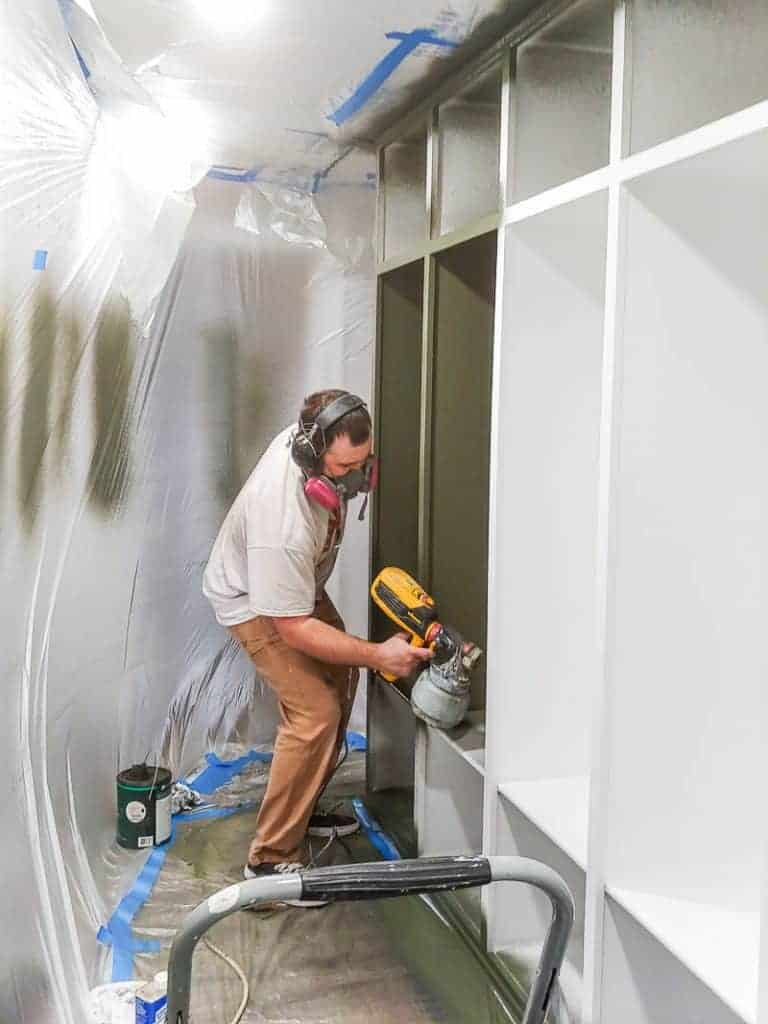shows a man using a paint sprayer to paint the shelves of the mudroom green with the rest of the room covered in plastics and tape