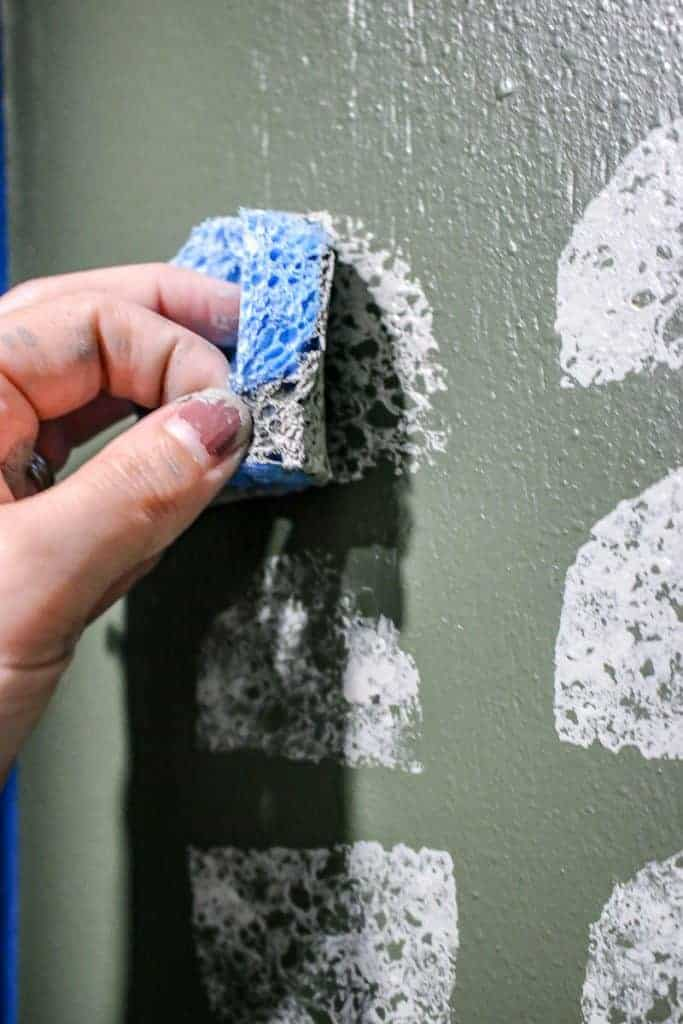 shows an up close picture of a hand stamping a gray painted half circle sponge to a green wall painted with other half circles