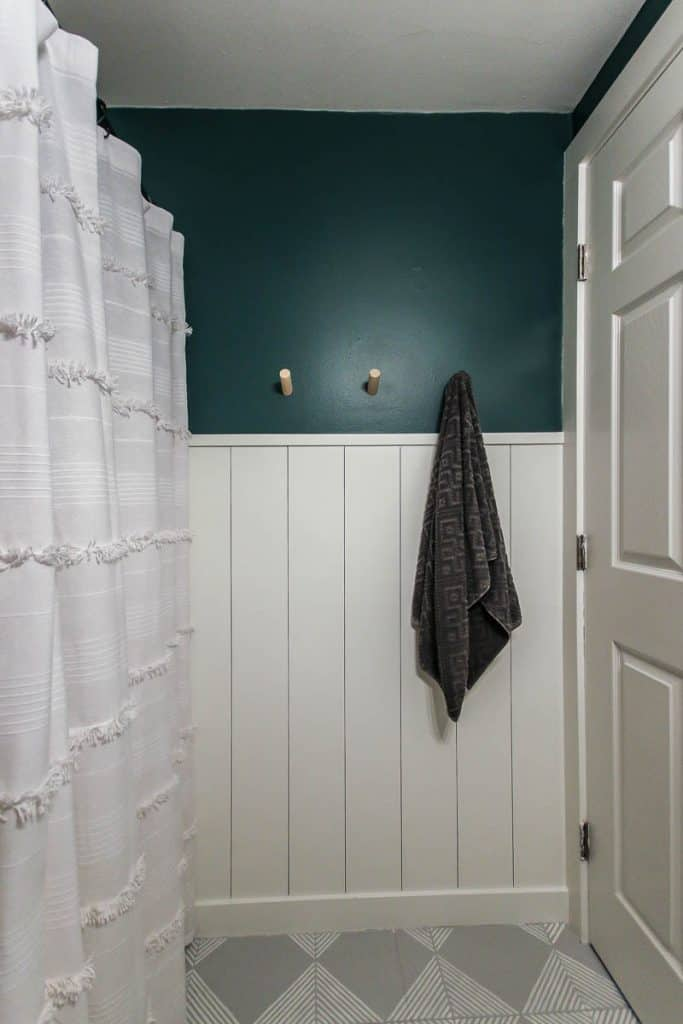 show white vertical shiplap half wall with top half painted dark green with a white door and shower curtain, wood hooks for towels, and gray painted tile floors with white stripes