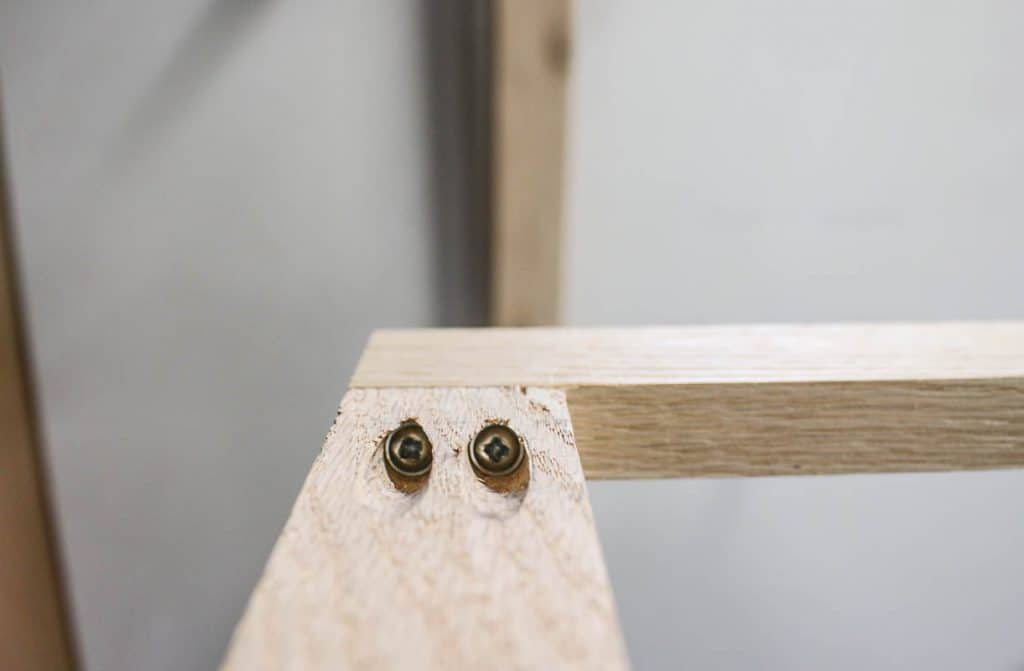 shows a view of the screws in the pocket holes connecting the two pieces of wood together