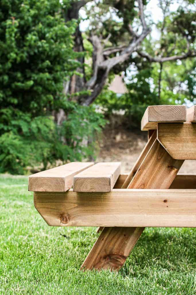 shows a side view of the toddler picnic table with a couple trees and grass in the background
