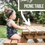 shows a side view of the toddler eating a Popsicle wearing a navy blue outfit on a wood picnic table on a boho black and white rug with overlay text that says how to build a kids picnic table and free plans