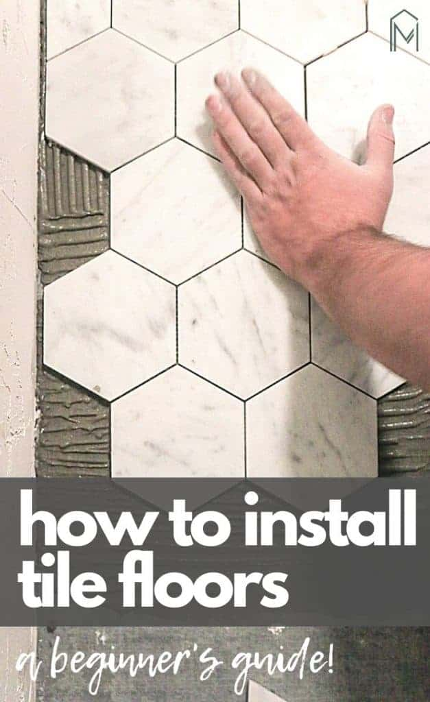 Man's hand pressing white marble hexagon tile onto floor with thin set mortar in a bathroom with text overlay that says how to install tile floors a beginner's guide