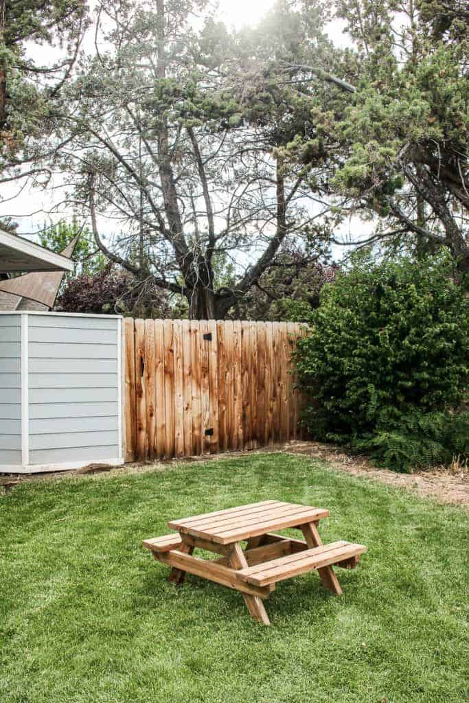 shows a backyard with wooden fence and grass with little wood kids picnic table