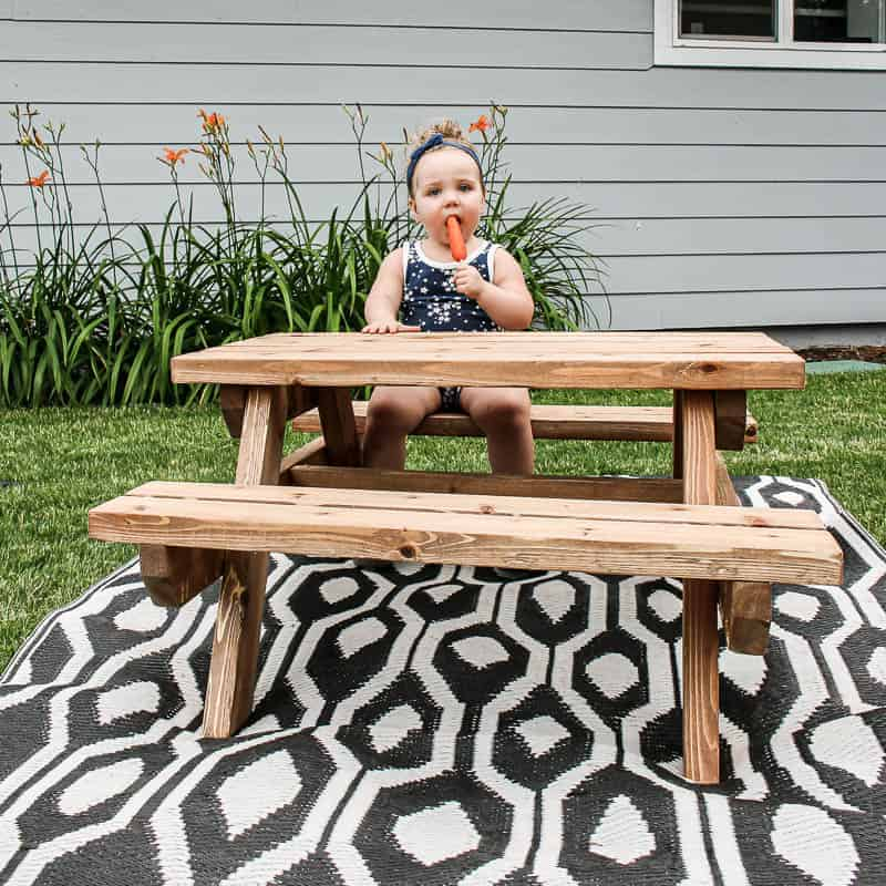 shows a front view of the toddler eating a Popsicle at a wood kids picnic table on a black and white boho rug with the side of the house in the background with orange flowers