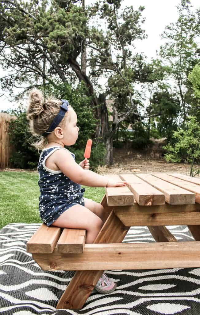 shows a side view of the toddler eating a Popsicle wearing a navy blue outfit on a wood outdoor toddler picnic table on a boho black and white outdoor rug over grass with trees in background