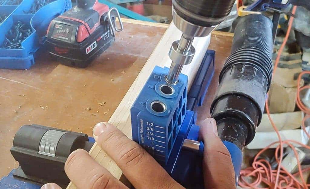 shows the kreg K5 pocket hole system drilling a hole in a piece of wood